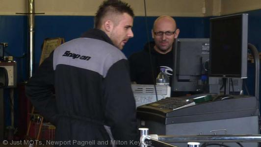 A photo of two employees performing an MOT at Just MOTs of Milton Keynes